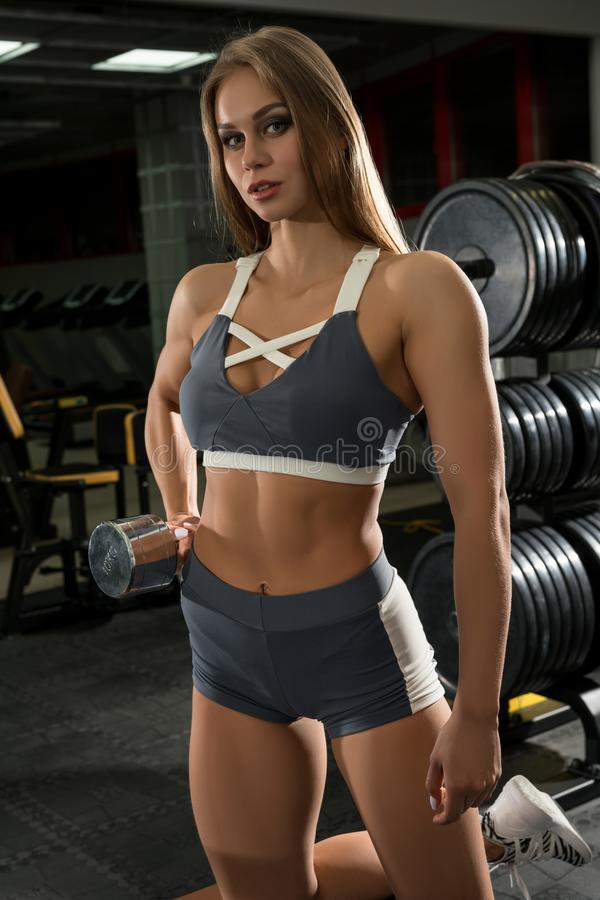 Muscular female exercising with dumbbell royalty free stock image
