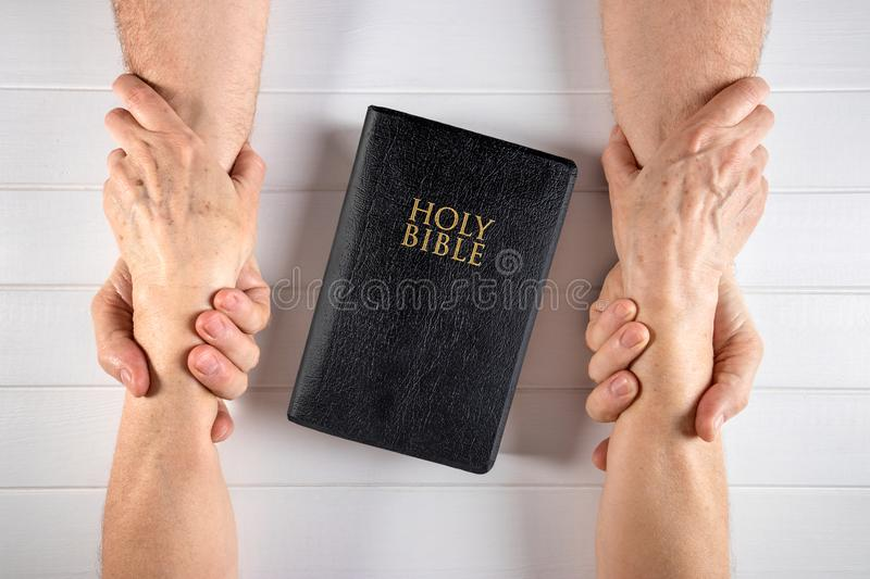 Strong relationship of a family to old age around the Word of Go. Old man and woman holding hands around a Holy Bible on white wood board royalty free stock images