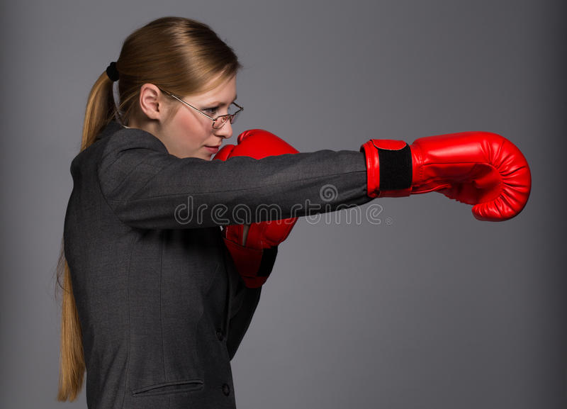 Strong and resolute young woman in dark grey business suit, glasses and red boxing gloves stands in fighting pose with punch stock photo