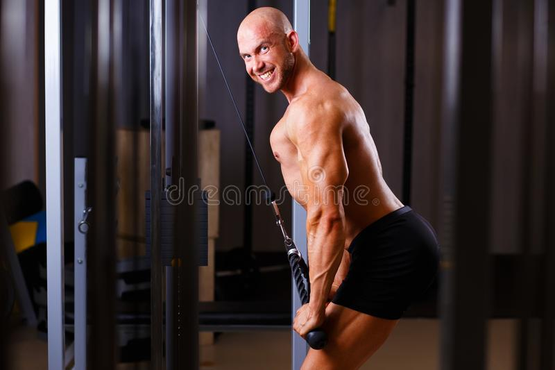 Strong ripped bald man pumping iron. Sports man bodybuilder smil. Ing and posing with equipment in gym. Sport, fitness, bodybuilding concept stock images