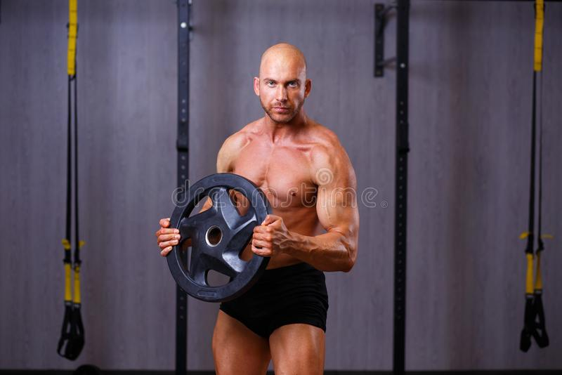 Strong ripped bald man pumping iron. Sports man bodybuilder posi. Ng with weight plate in gym. Sport, fitness, bodybuilding concept stock photography