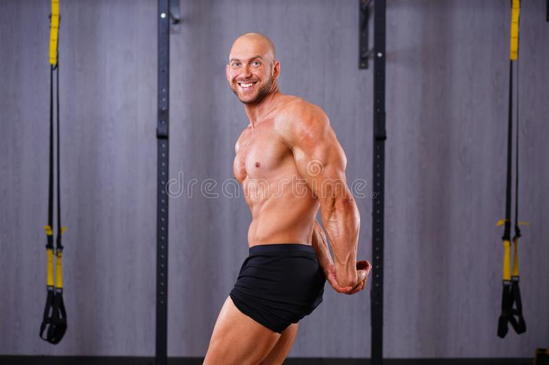 Strong ripped bold man demonstrating big muscles in gym. Sport, royalty free stock image