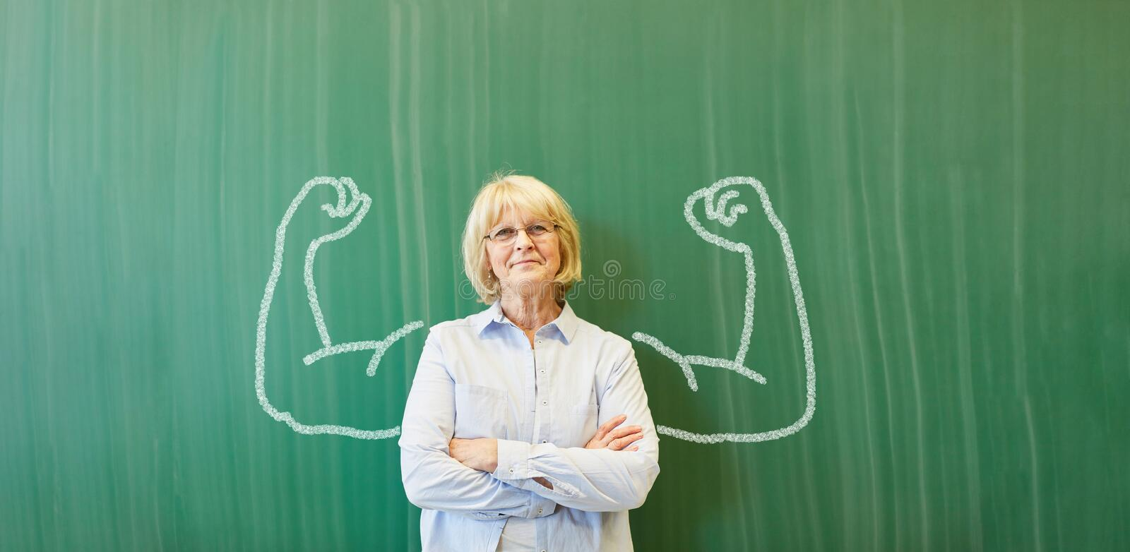 Strong senior teacher with chalk muscles. In front of chalkboard