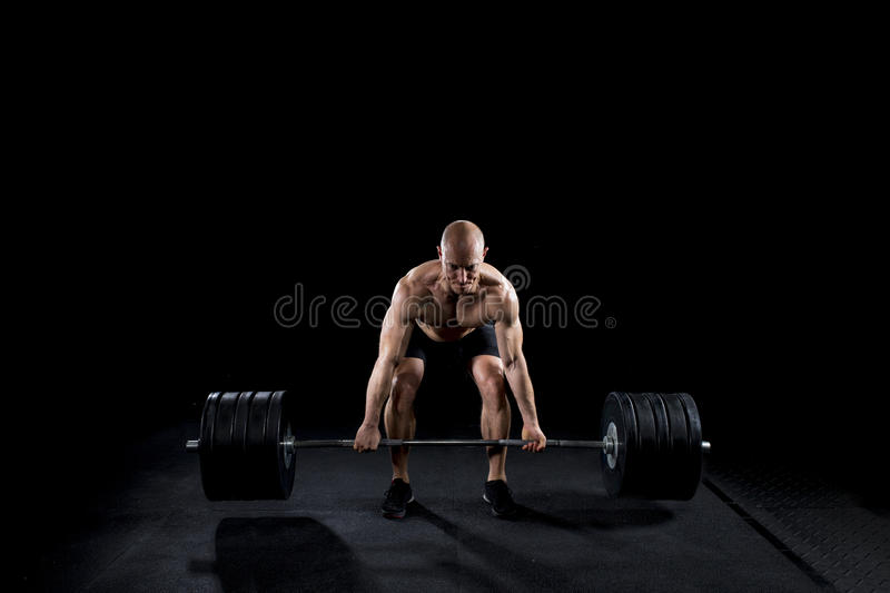 Strong man deadlifts a lot of weight royalty free stock images