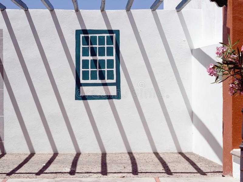 Strong shadows of a metal grid cast a graphic pattern on a white wall diagonally. From top left to bottom right, in the middle of the wall a window is painted royalty free stock image