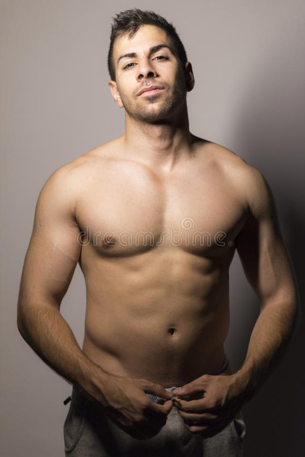 Strong shirtless man posing in night portrait royalty free stock images