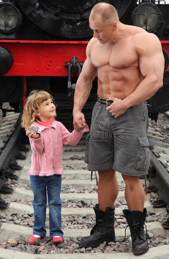 Download Strong Shirtless Man Stands On Railroad With Girl Stock Photo - Image: 11411528