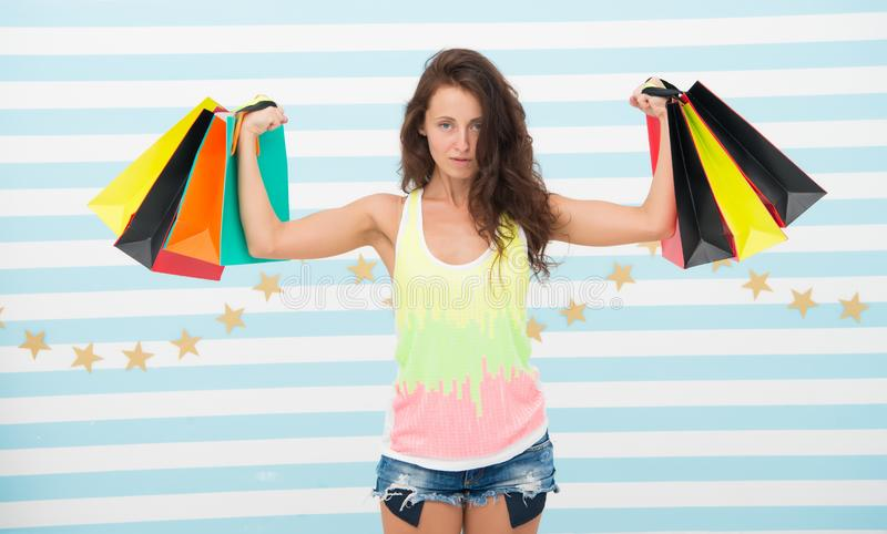 Strong shopaholic girl hold shopping bags. beautiful shopaholic. girl holding colorful paper bags in strong hands. power royalty free stock photography