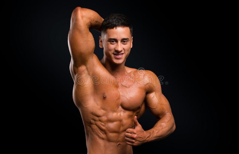 Strong smiley athletic man fitness model showing muscles on dark background.  royalty free stock image