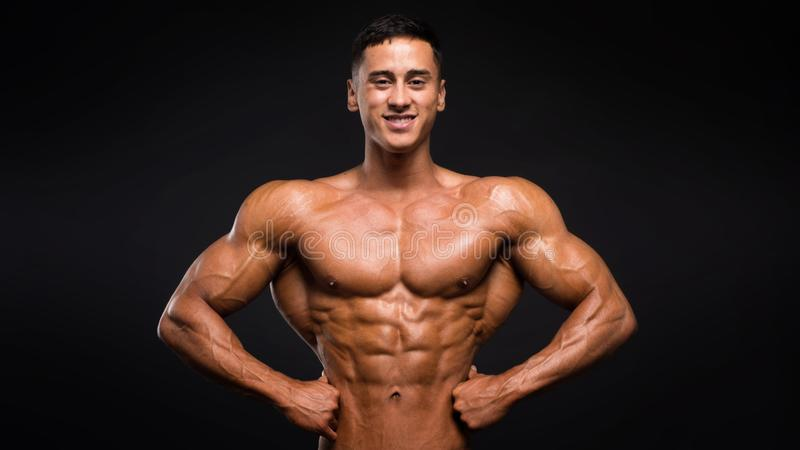 Strong smiley athletic man fitness model showing muscles on dark background.  stock photos