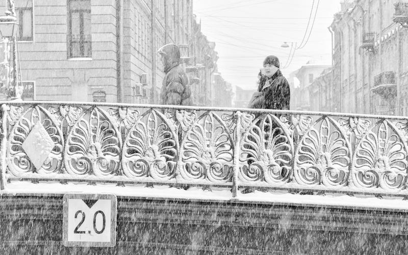 The strong snowstorm in Saint Petersburg. People walking along Demidov bridge. stock images