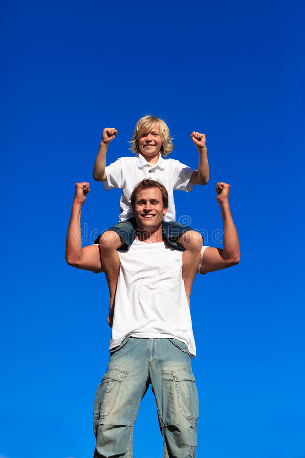 Strong son sitting on his father's shoulders stock images