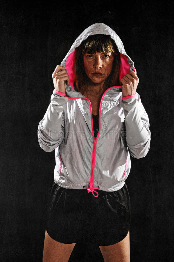 Strong sport freckles woman wearing training jacket hood on posing defiant. 40s fit and strong sport freckles woman wearing training jacket hood on posing royalty free stock photos