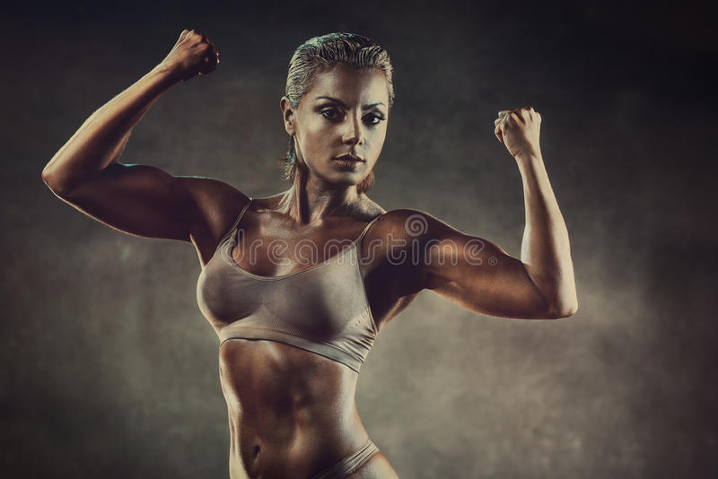 Strong sports woman. On wall background. Vintage film style colors effect stock image