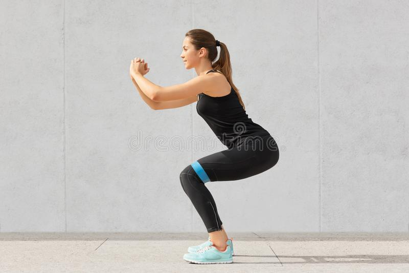 Strong sporty Caucasian woman has exercises with rubber resistance band, trains legs, works on muscles, dressed in t shirt and leg. Gings, stands indoor against stock photography