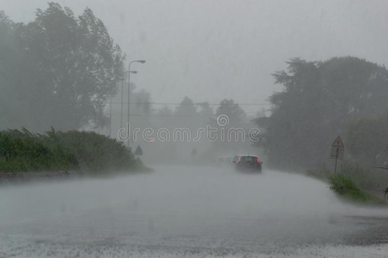 The strong storm with heavy rain on the road with poor visibility of cars. Concept of the danger of driving in bad weather, season, street, traffic, background stock images