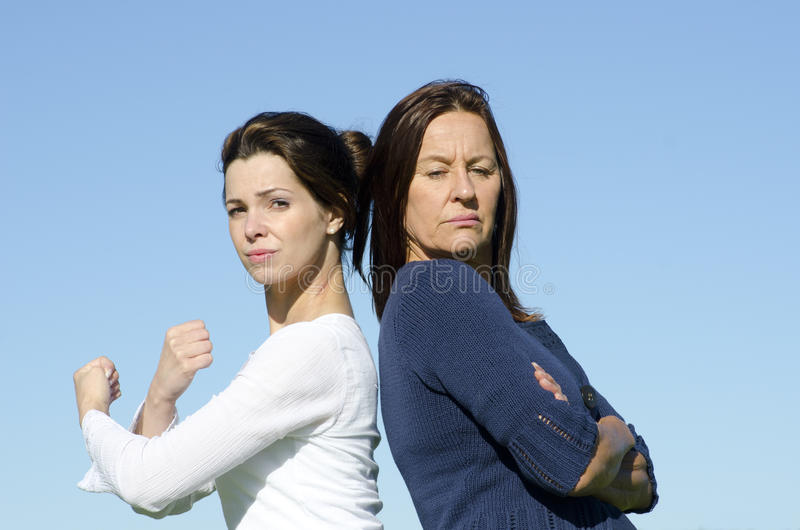 Strong and stubborn women back to back. Two attractive looking women, two generations, mother and daughter, standing back to back, with determined respectively stock photos