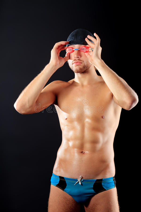Strong swimmer. Portrait of a man professional swimmer over black bakground royalty free stock photo