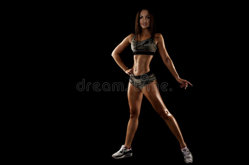 Strong tanned beautiful sports girl on a black background. Copy space stock image