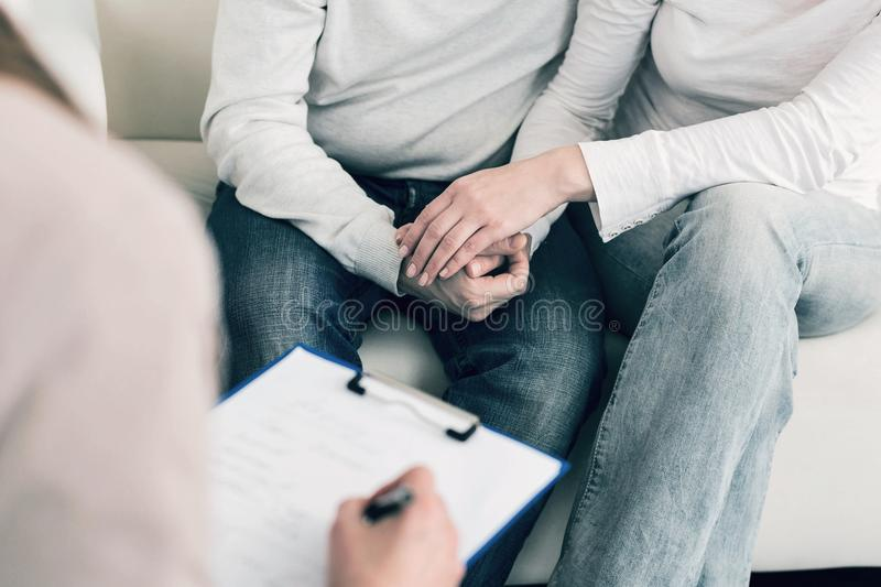 Close up of couple that visiting psychologist. We are strong. Two people holding hands and sitting close to each other while consulting with their doctor stock photo