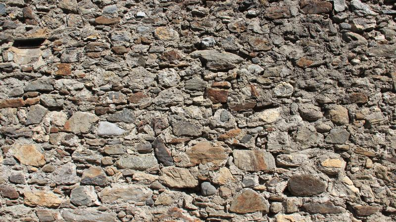 Old stron Stone Walls In Historic Old Town. Strong walls. sunlight and old stone walling in historic old town. Tirano Italy royalty free stock photography