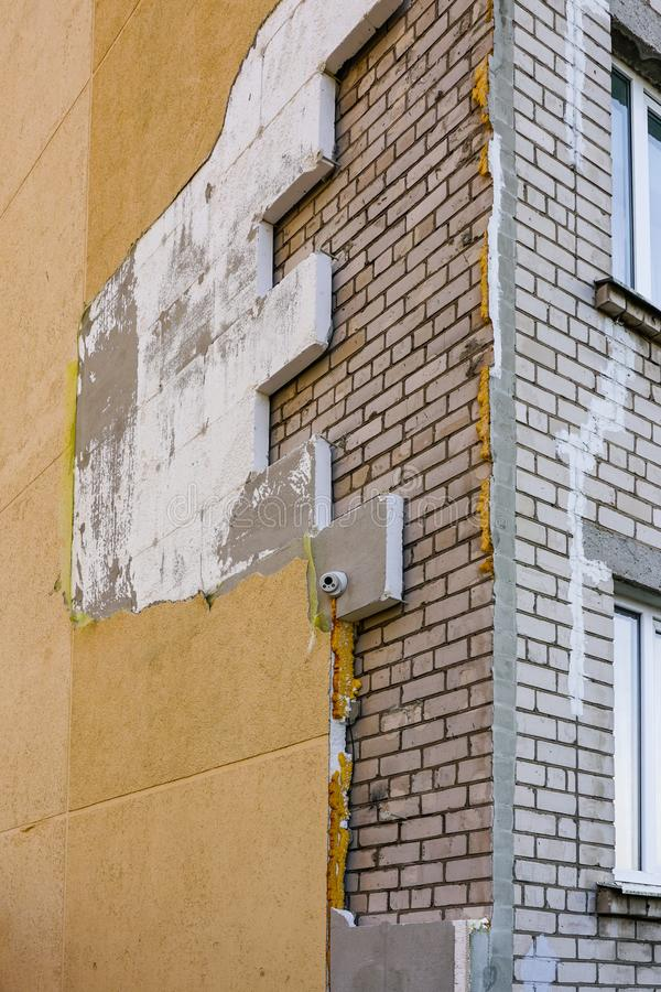 Strong wind or poor quality of work damaged building thermal insulation. Strong wind or poor quality of work damaged apartment building thermal insulation stock images