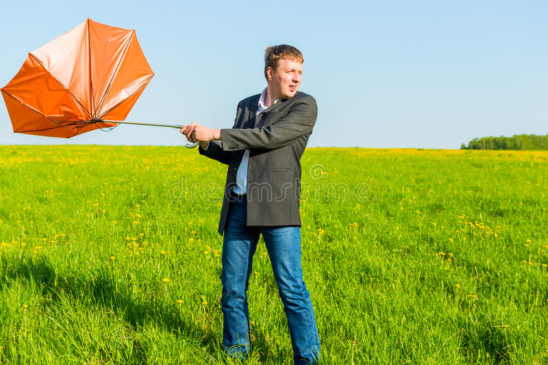 Strong wind wrenched umbrella man stock images