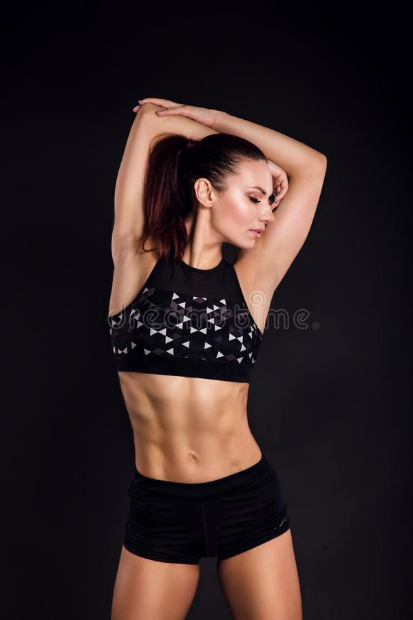 Strong woman bodybuilder with perfect abs, shoulders, biceps, triceps and chest. Photo of sporty young woman on black. Background. Strength and motivation royalty free stock photos
