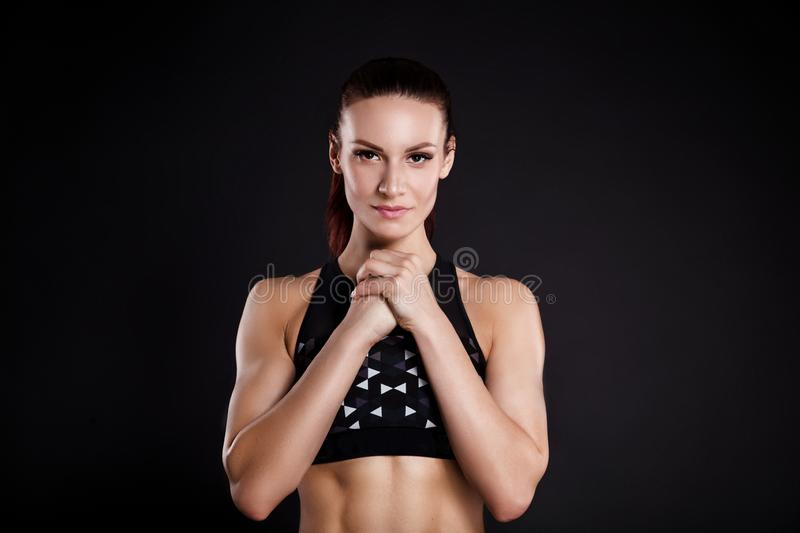 Strong woman bodybuilder with perfect abs, shoulders, biceps, triceps and chest. Photo of sporty young woman on black. Background. Strength and motivation stock image