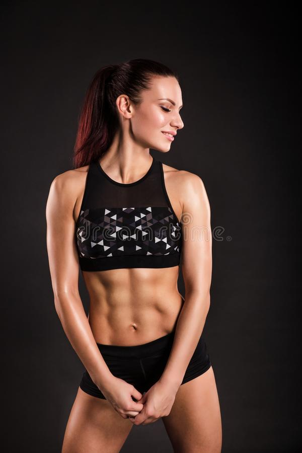 Strong woman bodybuilder with perfect abs, shoulders, biceps, triceps and chest. Photo of sporty young woman on black. Background. Strength and motivation royalty free stock images