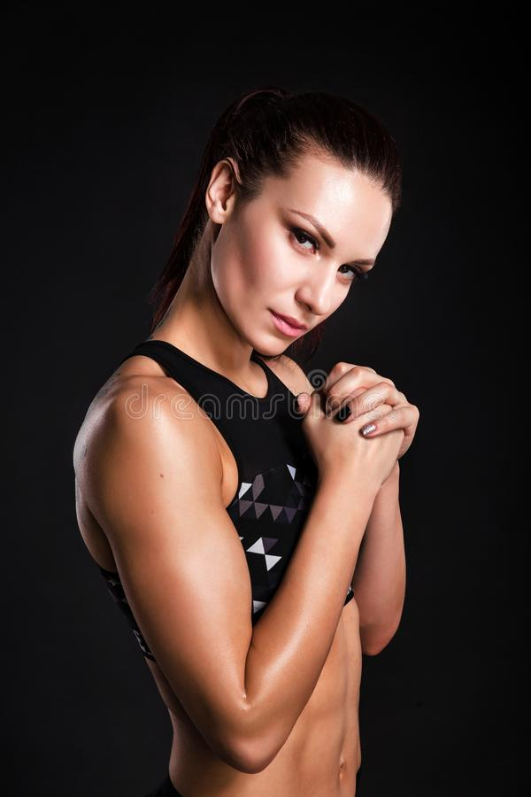 Strong woman bodybuilder with perfect abs, shoulders, biceps, triceps and chest. Photo of sporty young woman on black. Background. Strength and motivation royalty free stock photography
