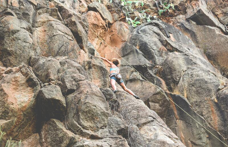 Strong woman climbing a rock wall in a canyon - Climber training outdoor - Travel, adrenaline and extreme dangerous sport concept. Focus on her body stock image
