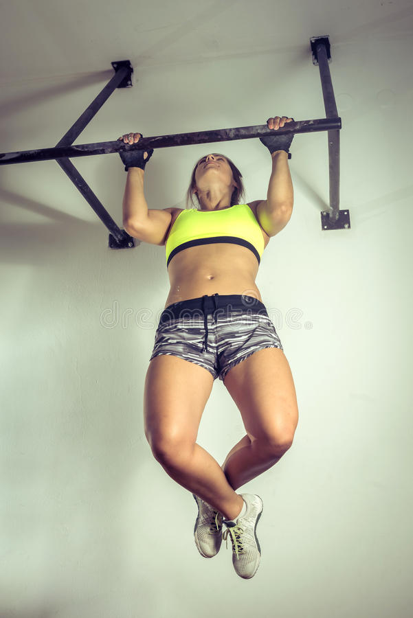 Strong woman doing pull ups. stock photo