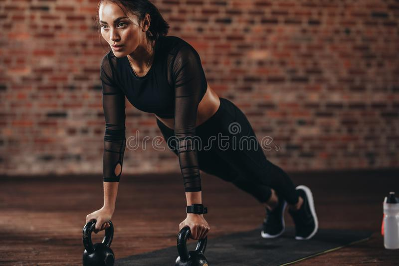 Strong woman doing push-ups on kettle bell. In gym. Muscular female exercising in health club stock photo