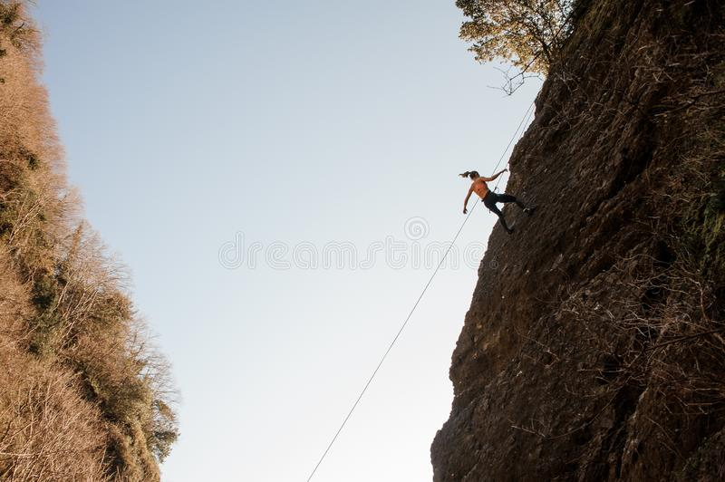 Strong woman equipped with a rope abseiling on the sloping rock stock photography