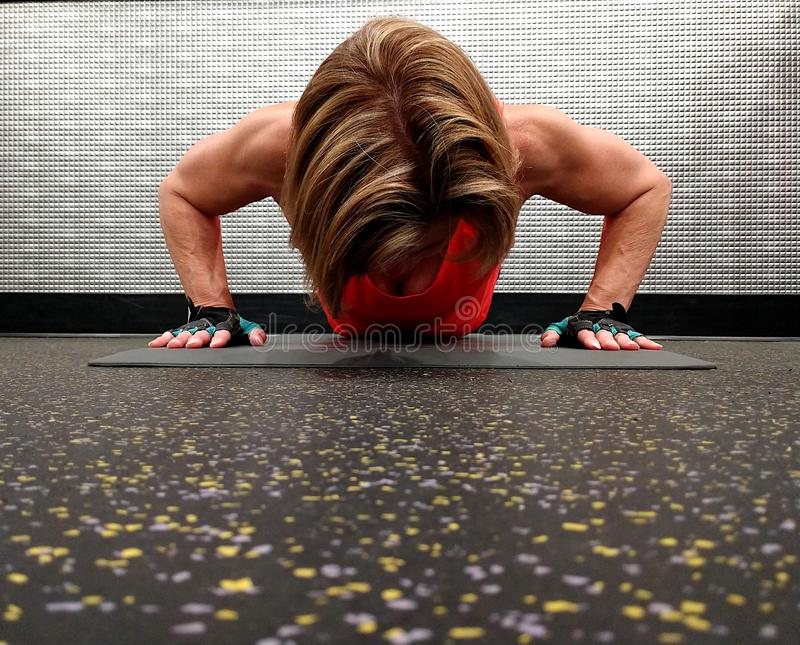 A strong woman exercising in the push up position. stock image