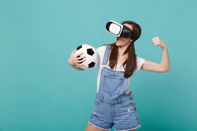 Strong woman football fan in headset holding soccer ball, showing biceps, muscles isolated on blue turquoise background. People emotions, sport family leisure royalty free stock photography