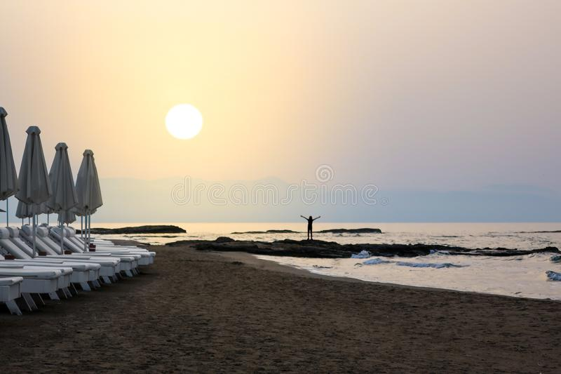 Strong woman / girl open arms, embrace the sunrise at seaside. royalty free stock image