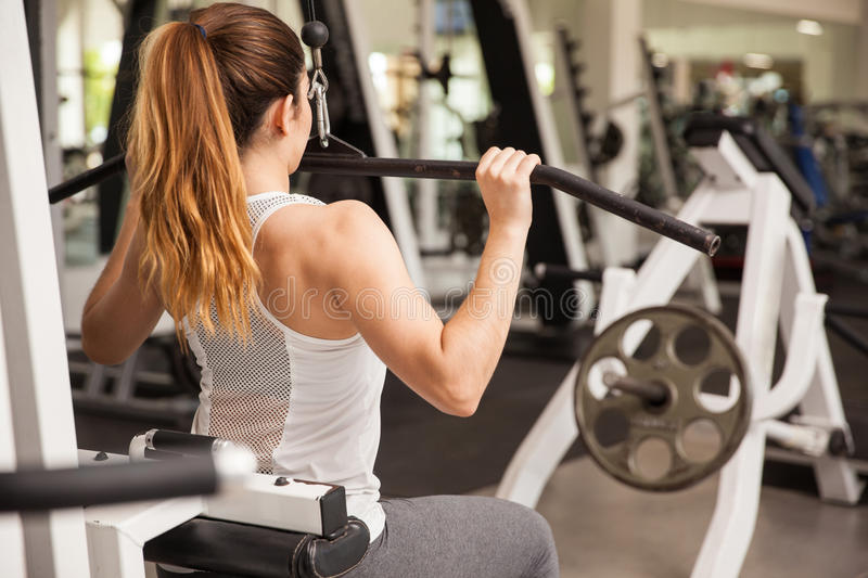 Strong woman on a lat pulldown machine royalty free stock photos