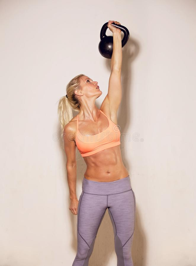 Strong Woman Lifting a Kettlebell stock photography