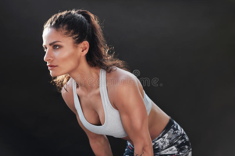 Strong woman with muscular body. Shot of a strong woman with muscular body in sportswear. Fitness female model posing on black background royalty free stock photos