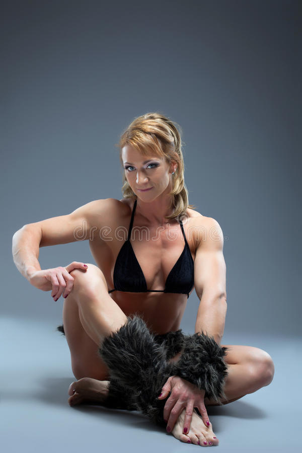 Strong woman relax in amazon fur costume stock photo