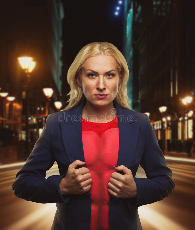 Strong woman. Superhero showing off her strength in night city street royalty free stock photo