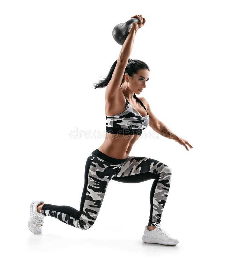 Strong woman training muscles of hands and legs using a kettlebell. Photo of attractive woman in fashionable sportswear isolated on white background. Strength stock images