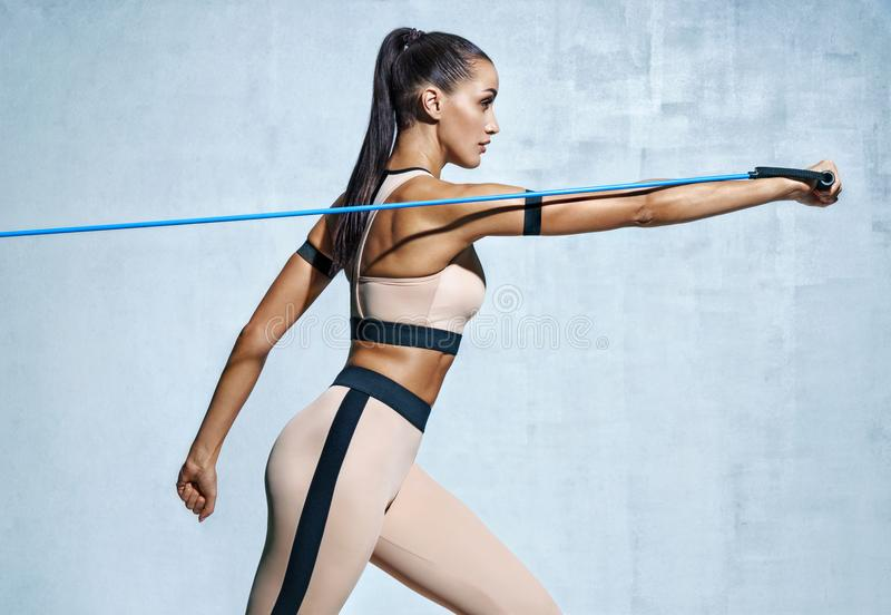 Strong woman using resistance band in her exercise routine royalty free stock images