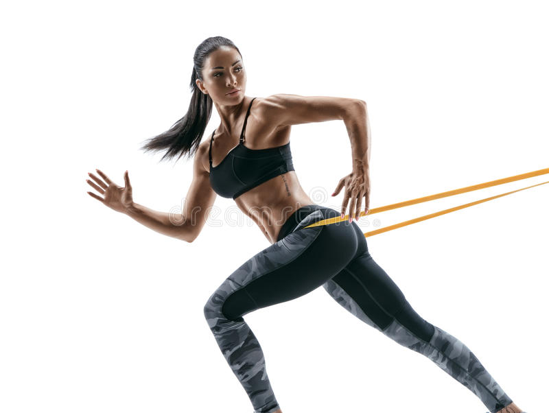 Strong woman using a resistance band in her exercise routine. Young woman performs fitness exercises on white background stock image