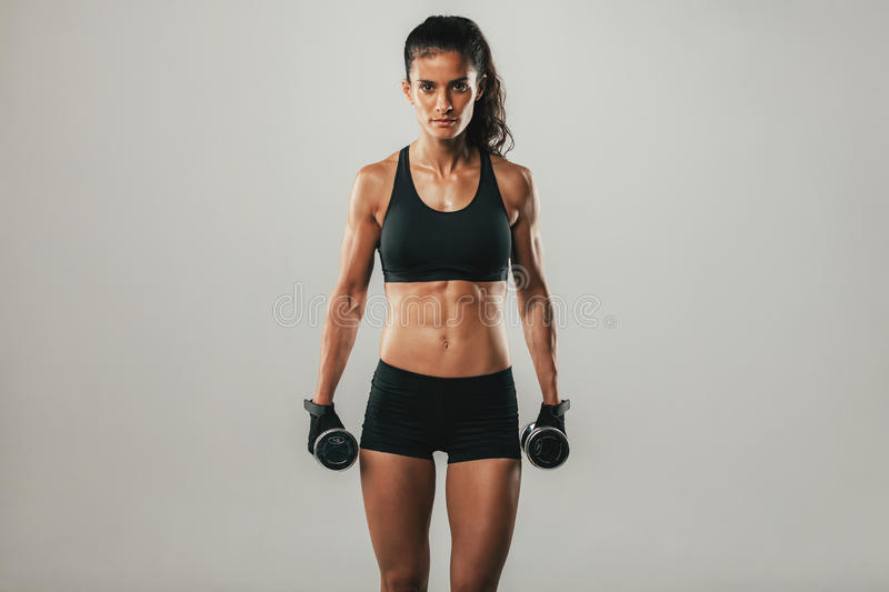 Strong woman with weights and confident expression. Strong woman with pair of black dumbbell weights and confident expression standing over gray background with stock photo