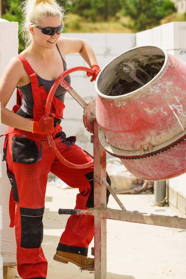 Strong woman working with construction site. Strong woman worker working with red concrete cement mixer machine on house construction site. Industrial work stock image