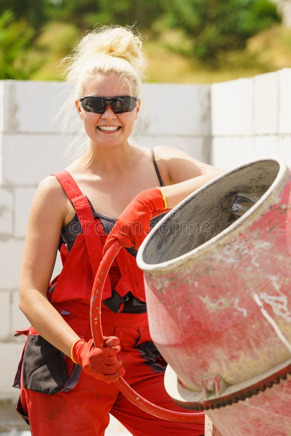 Strong woman working with construction site. Strong woman worker working with red concrete cement mixer machine on house construction site. Industrial work royalty free stock photo