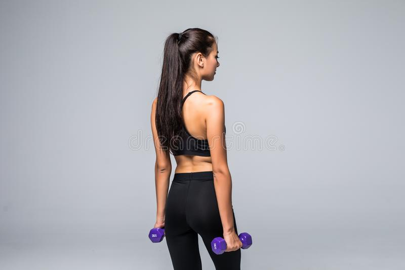 Strong woman working out with dumbbells, flexing her arm. Sporty woman in sportswear on grey background. Rear view royalty free stock photo